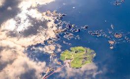 Waterspiegel, de bezinning van de hemel en het groene Leliestootkussen stock afbeelding