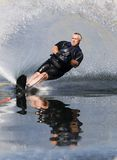 Watersports. Action waterskier with large spray and reflection in water Stock Image
