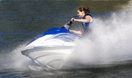 Watersports. Action shot of young woman on jetski/seadoo Royalty Free Stock Photo