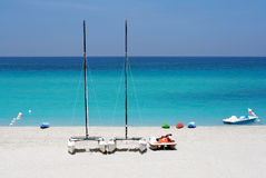 Watersports boats in a beach. Katamarans and water bicycles in a beach Royalty Free Stock Images