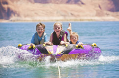 Watersports Fun - Kids Tubing. Three kids having a blast at the lake while tubing behind the family motorboat royalty free stock photo