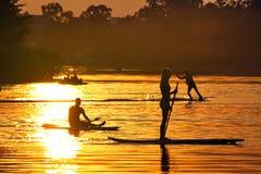 Watersportsathlets bij zonsondergang het wakeboarding en SUP Royalty-vrije Stock Fotografie