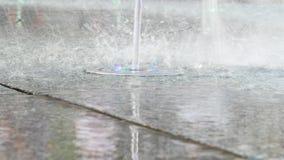 Waterstralen uit de grond met lichten zijn gebarsten dat De fontein van de stad stock footage