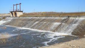 Waterstromen door de dam op rivier stock footage