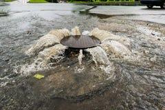 Waterstromen over de weg van het riool Stock Foto