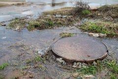 Waterstromen uit het mangat stock afbeelding