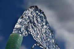 Waterstromen van de tuinslang Verkwistend verspillend water Globaal het verwarmen tekort aan water stock foto