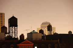 Watertanks and new york skyline at night stock photography