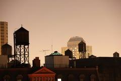 Watertanks und New- YorkSkyline nachts Stockfotografie