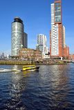 A watertaxi passing on an unusual warm Saturday in February at the Head of South in Rotterdam. A watertaxi is passing the old building on the uttermost point of royalty free stock photography
