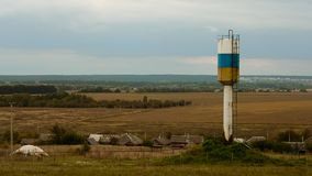 Village watertower in the fields. Watertower stand near the village. Some fields behind. Weather is cloudy royalty free stock photography