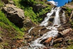 Waterval in de bergen tegen de hemel met wolken Stock Fotografie