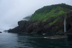 Waterval het dalen van hoge rotsachtige klippen in het oceaanoverzees van Okhotsk rond het Shiretoko-Schiereiland stock foto's