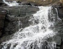Waterval met kleurrijke rotsen stock afbeeldingen