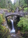 Waterval onder een steenbrug stock afbeeldingen