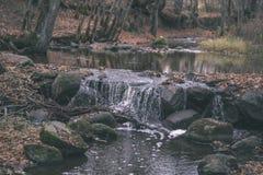 waterval over de rotsen in rivierstroom in bos in de recente herfst met naakte bomen en grijze kleuren in aard - uitstekende oude royalty-vrije stock fotografie
