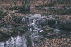 waterval over de rotsen in rivierstroom in bos in de recente herfst met naakte bomen en grijze kleuren in aard - uitstekende oude royalty-vrije stock afbeelding