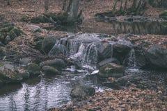 waterval over de rotsen in rivierstroom in bos in de recente herfst met naakte bomen en grijze kleuren in aard - uitstekende oude stock foto