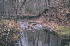 waterval over de rotsen in rivierstroom in bos in de recente herfst met naakte bomen en grijze kleuren in aard - uitstekende oude royalty-vrije stock foto