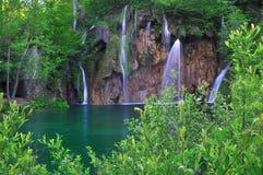 Watervallen in een groen meer Stock Foto