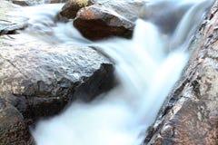 Watervallen over rotsachtig gewas Stock Foto