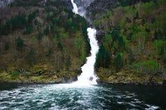 Watervalstromen neer onder de bergen - Flam in Noorwegen Stock Fotografie