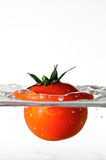 Watervegetable. A tomato falls into clear and fresh water Royalty Free Stock Photography