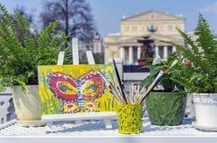 Waterverfborstels en schildersezel op de achtergrond van het Bolshoi-Theater in Moskou royalty-vrije stock afbeeldingen