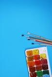 Waterverfverven en Borstels op blauwe achtergrond Stock Fotografie