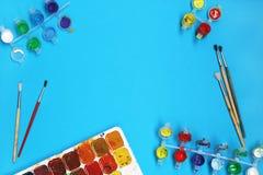 Waterverfverven en Borstels op blauwe achtergrond Stock Afbeelding