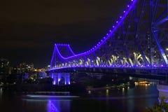 Waterverkeer 's nachts onder blauwe lichte brug stock afbeelding