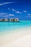 Watervilla's in het oceaan en witte zandige strand Stock Afbeeldingen