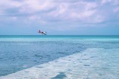 Watervliegtuig die bij mooi het eilandstrand van de Maldiven landen royalty-vrije stock afbeelding