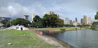 Waterway with bridge leads to pond in Ala Moana Beach Park. Surrounded by trees with Condominiums towers across the street on a nice day on Oahu, Hawaii Stock Image