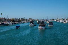 Waterway near Balboa Island with numerous pleasure boats docked along the sides and in the center of the waterway. Balboa Island, California - October 12, 2018 royalty free stock photo