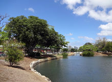 Waterway opens into pond in Ala Moana Beach Park. Surrounded by trees on a nice day on Oahu, Hawaii Stock Image