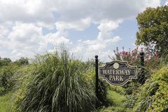 Waterway Park Sign in Beautiful Foliage. Oak Island, NC, USA - July 29, 2014: Waterway Park sign on signposts in lush vegetation and flowers. Sunny day in Stock Photography
