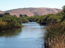 Waterway slough with hills Royalty Free Stock Images