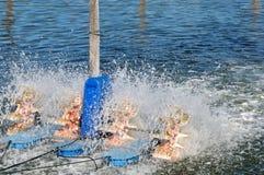 Waterwheel работая в пруде для разведения рыбы Стоковая Фотография