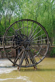The waterwheel. An Chinese antique wood waterwheel by the rivulet bank Royalty Free Stock Photo