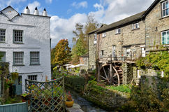 Waterwheel at Ambleside, English Lake District. A small stream with lush vegetation, overlooked by attractive buildings and a waterwheel, at Ambleside in the Royalty Free Stock Image