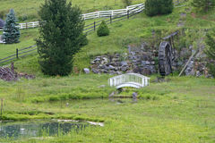 Waterwheel, Bridge, Pond. A white arched footbridge and pond in front of a waterwheel Royalty Free Stock Photography