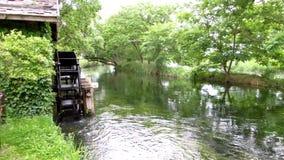 Waterwheel. Wooden waterwheel at the riverside stock footage
