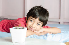 wating为新的婴孩植物的小亚裔男孩长大 免版税库存照片
