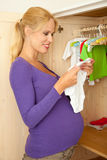 Wating for the big day. Beautiful pregnant woman with baby clothes Stock Photos