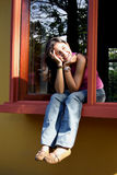 Wating at the window. Teenager sited at the window Royalty Free Stock Photography