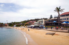 Watson Bay. Coast scenery with sandy beach, palms, boat, restaurants and people Stock Photography