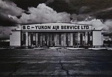 Watson Lake, Yukon, Canada airport hanger. Watson Lake, Yukon, Canada airport with World War Two era hanger and blue skies stock photos