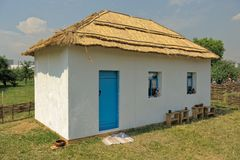 Wattle and daub hut. White hut, house, dwelling, with a thatched roof, on a sunny day Stock Images