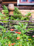 Wattle hurdle with clay pot and old cottage Royalty Free Stock Photos